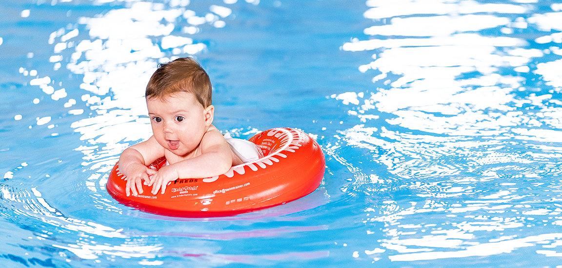Fröhliches Baby im Wasser. Schwimmen im Swimtrainer.