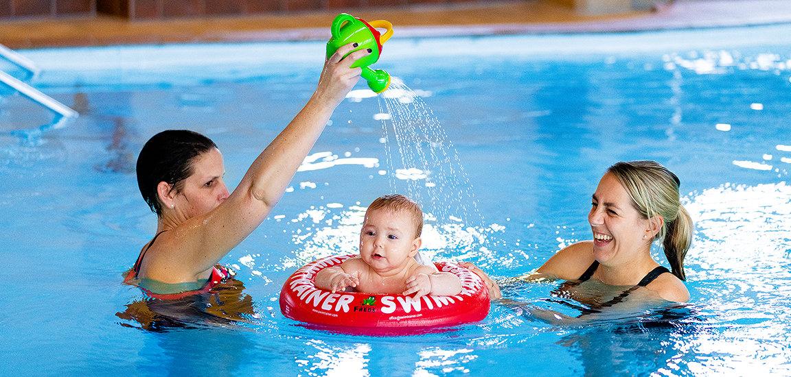 Baby im Swimtrainer. Mutter mit Baby beim Babyschwimmen.