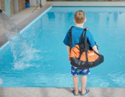 Kind mit Tasche vor Pool