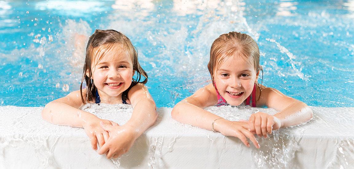 Fröhliche Kinder im Wasser im Kinderschwimmkurs.